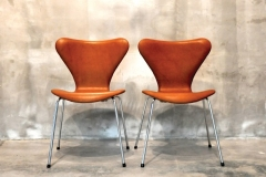 ARNE JACOBSEN Series 7 Chair, Model 3107, Set of 2 Tan Aniline leather, chrome-plated steel, plastic Signed with molded manufacturer's mark to frame of each example- [Made in Denmark by Fritz Hansen] 79 x 51 x 47 cm
